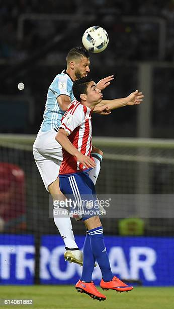 Argentina's Martin Demichelis and Paraguay's Miguel Almiron vie for the ball during their Russia 2018 World Cup football qualifier match in Cordoba...