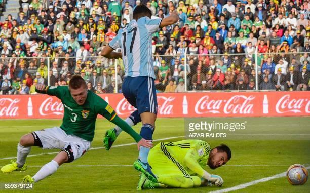 Argentina's Matias Caruzzo and goalkeeper Sergio Romero vie for the ball with Bolivia's Alejandro Chumacero during their 2018 FIFA World Cup...