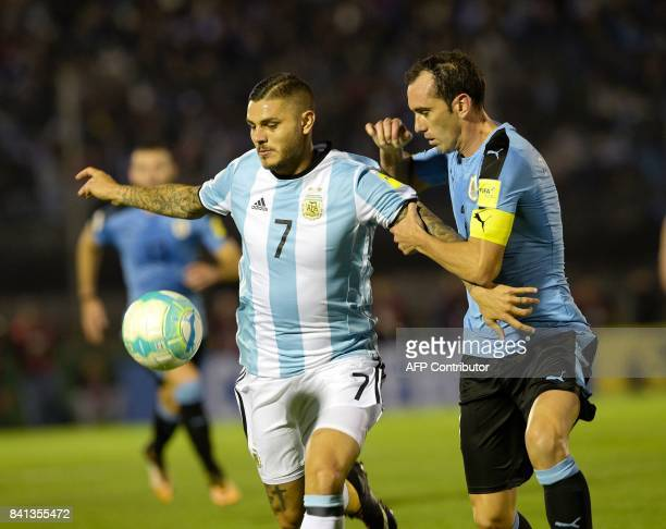 Argentina's Mauro Icardi and Uruguay's Diego Godin vie for the ball during their 2018 World Cup qualifier football match in Montevideo on August 31...