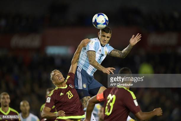 Argentina's Mauro Icardi and Venezuela's Rolf Feltscher vie for the ball during their 2018 World Cup qualifier football match in Buenos Aires on...