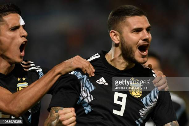 Argentina's Mauro Icardi celebrates with teammate Erik Lamela after scoring against Mexico during their friendly football match at the Malvinas...