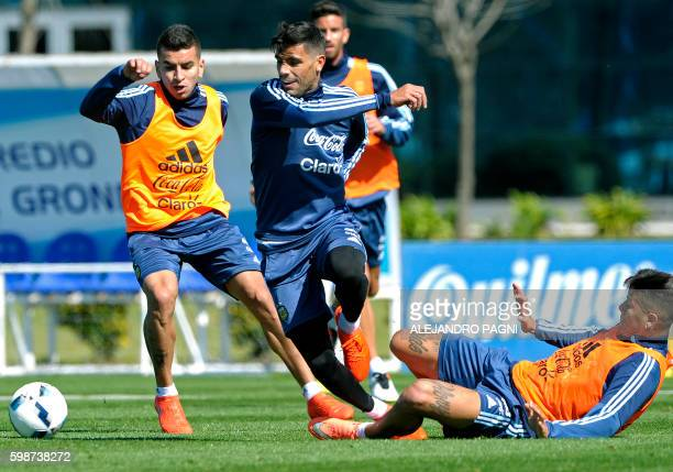 Argentina's midfielder Augusto Fernandez vies for the ball with Argentina's forward Angel Correa and defender Marcos Rojo during a training session...