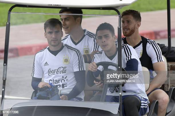 Argentina's midfielder Cristian Pavon drives a cart with teammates defender Nicolas Taglafico forward Paulo Dybala and defender Cristian Ansaldi as...