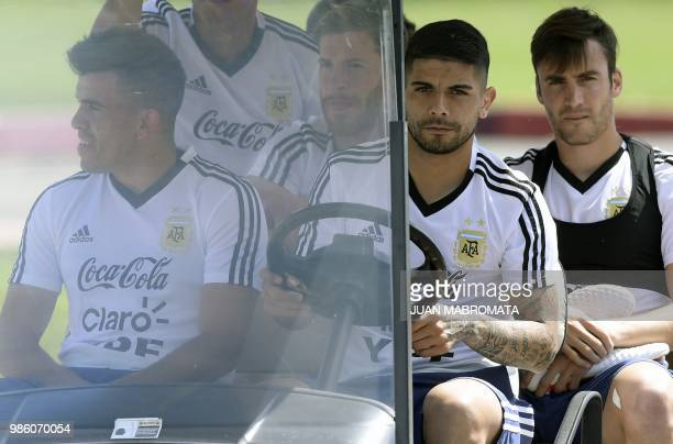 Argentina's midfielder Ever Banega drives a cart with defender Marcos Acuna defender Nicolas Taglafico and defender Cristian Ansaldi as they arrive...