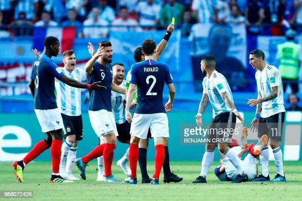 Argentina's midfielder Ever Banega is handed a yellow card by Iranian referee Alireza Faghani during the Russia 2018 World Cup round of 16 football...
