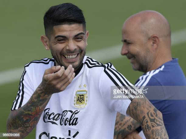 Argentina's midfielder Ever Banega reacts next coach Jorge Sampaoli during a training session at the team's base camp in Bronnitsy near Moscow on...