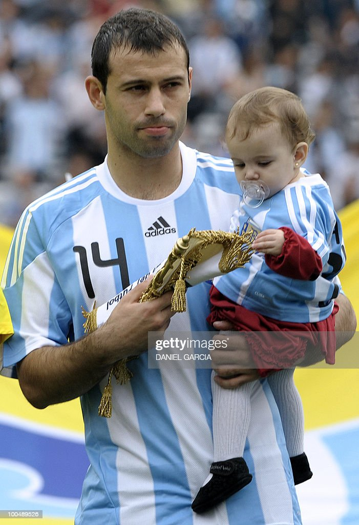 Argentina's midfielder Javier Mascherano carries his daughter in his arms before a friendly football match against Canada at the Monumental stadium in Buenos Aires, on May 24, 2010. Argentina is flying to South Africa for the World Cup finals on Friday, and will play their first match against Nigeria on June 12 in Johannesburg. AFP PHOTO/Daniel GARCIA