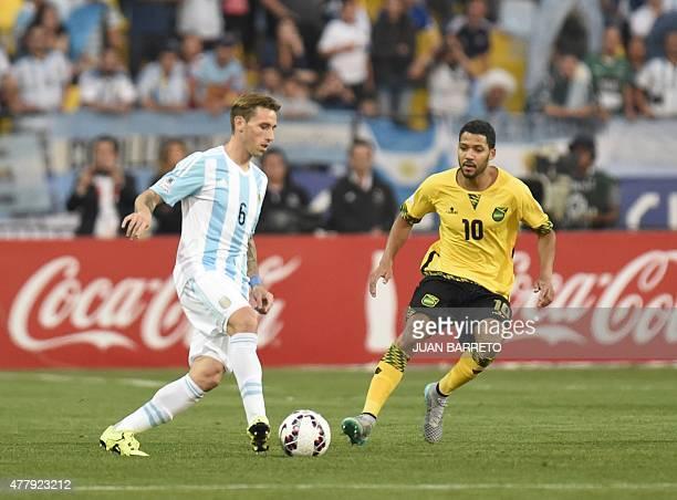 Argentina's midfielder Lucas Biglia and Jamaica's midfielder Joel McAnuff vie for the ball during their 2015 Copa America football championship match...
