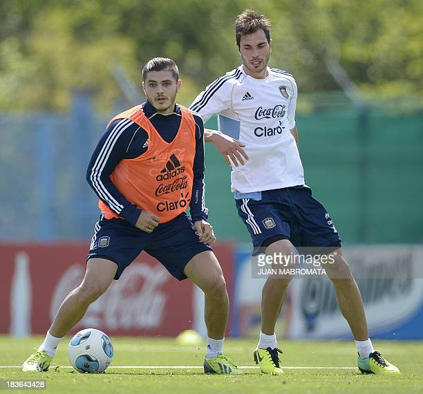 Argentina's midfielder Mauro Icardi and defender Jose Basanta vie for the ball during a training session in Ezeiza Buenos Aires on October 8 2013...