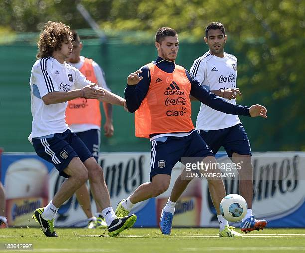 Argentina's midfielder Mauro Icardi strikes the ball next to defender Fabricio Coloccini during a training in Ezeiza Buenos Aires on October 8 2013...