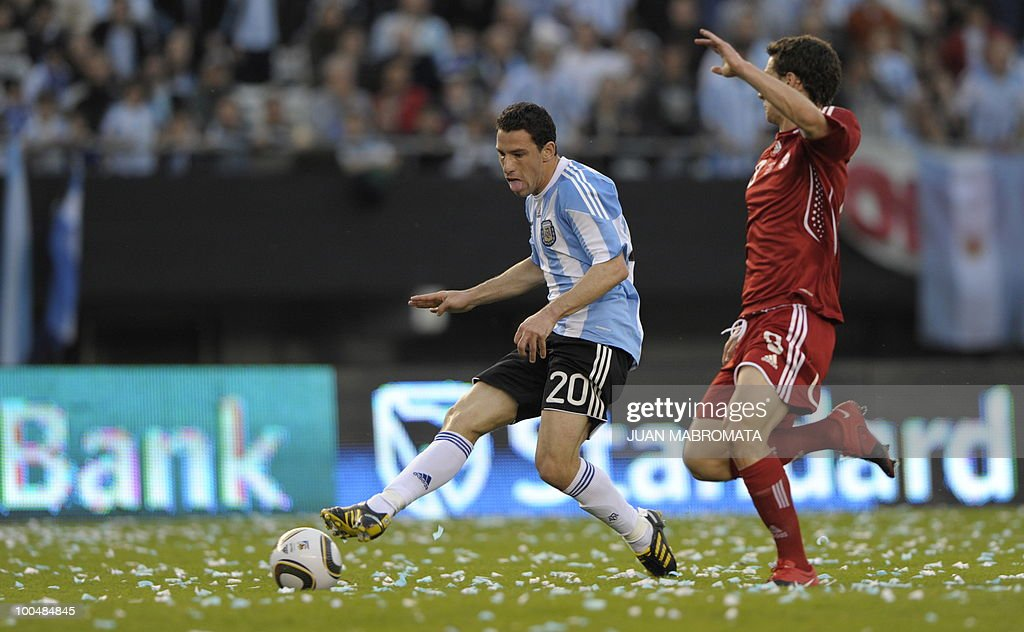 Argentina's midfielder Maxi Rodriguez (L) strikes next to Canada's forward Will Johnson to score the team's second goal during a friendly football match at the Monumental stadium in Buenos Aires, on May 24, 2010. Argentina is flying to South Africa for the World Cup finals on Friday, and will play their first match against Nigeria on June 12 in Johannesburg. AFP PHOTO / Juan Mabromata