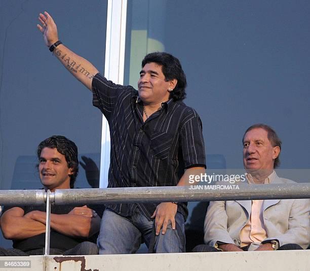 Argentina's national football team coach Diego Maradona waves to the crowd amid Argentine former footballer Alejandro Mancuso and Argentine national...