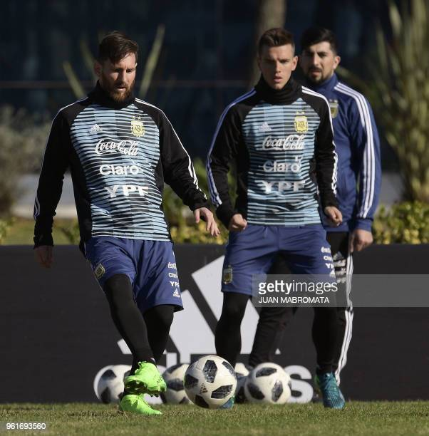Argentina's national football team forward Lionel Messi passes the ball next to midfielder Giovani Lo Celso during a training session in Ezeiza...