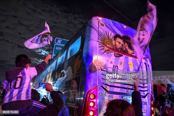 TOPSHOT Argentina's national football team supporters cheer as the bus transporting the team sparrings leave the Argentine Football Association...
