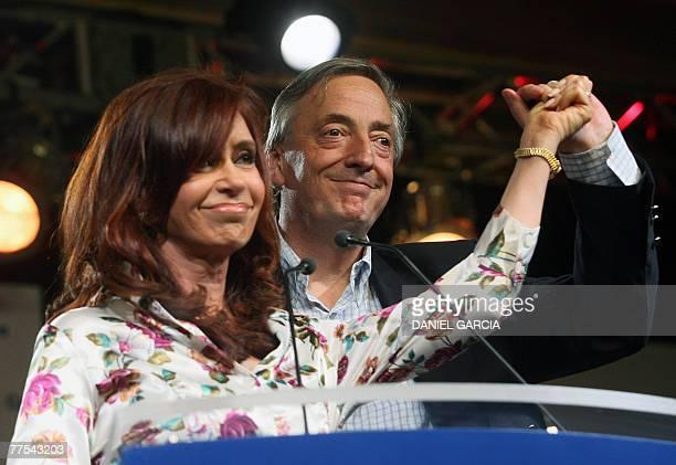 Argentina's newly elected president Cristina Fernandez de Kirchner and her husband president Nestor Kirchner greet supporters 28 October 2007 in...