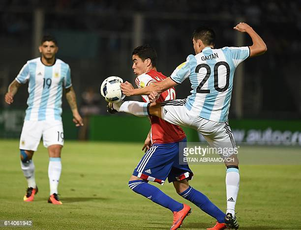 Argentina's Nicolas Gaitan vies for the ball with Paraguay's Miguel Almiron during their Russia 2018 World Cup football qualifier match in Cordoba...