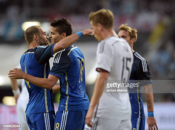 Argentina's Pablo Zabaleta and Erik Lamela embrace each other as Germany's Erci Durm looks on after the international match between Germany vs...