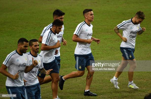 Argentina's Paolo Dybala runs with teammates during a training session at the National Stadium in Singapore on June 12 2017 Argentina will play...