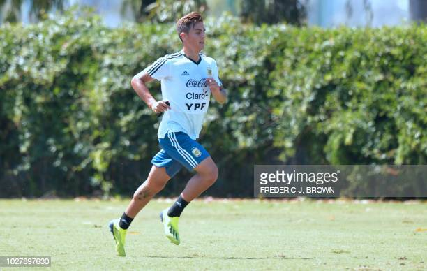 Argentina's Paulo Dybala holds a stopwatch while running during a training session in Carson California on September 6 ahead of the international...