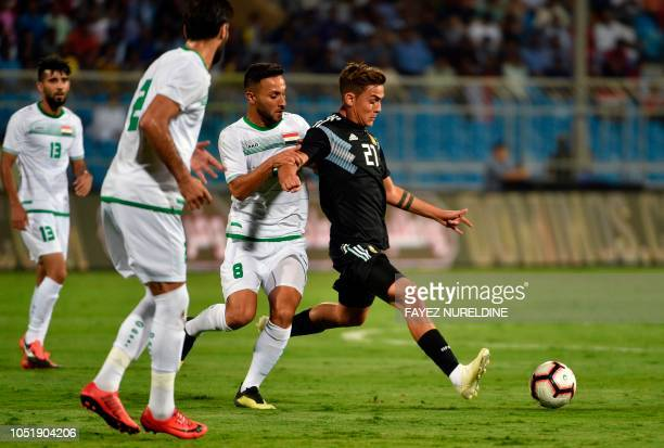 Argentina's Paulo Dybala is marked by Iraq's Osama Rashid during a friendly football match between Argentina and Iraq at the Faisal bin Fahd Stadium...