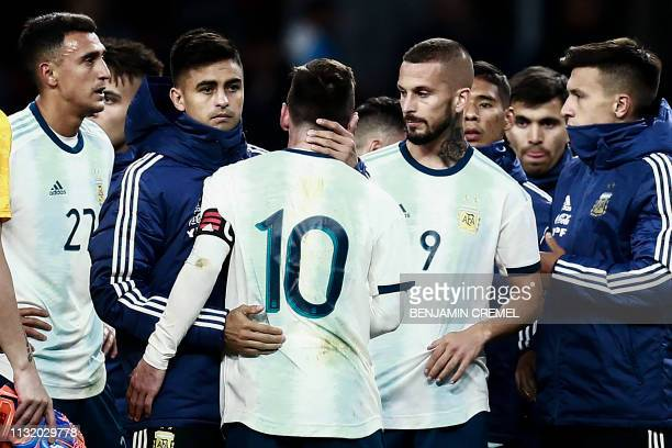 Argentina's players console Argentina's forward Lionel Messi at the end of an international friendly football match between Argentina and Venezuela...