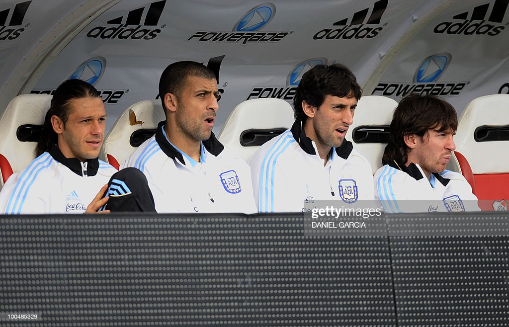 Argentina's players defender Martin Demichelis, defender Walter Samuel, forward Diego Milito and forward Lionel Messi watch from the sustitute bench, before a friendly match against Canada at the Monumental stadium in Buenos Aires, on May 24, 2010. Argentina is flying to South Africa for the World Cup finals on Friday, and will play their first match against Nigeria on June 12 in Johannesburg. AFP PHOTO/Daniel GARCIA