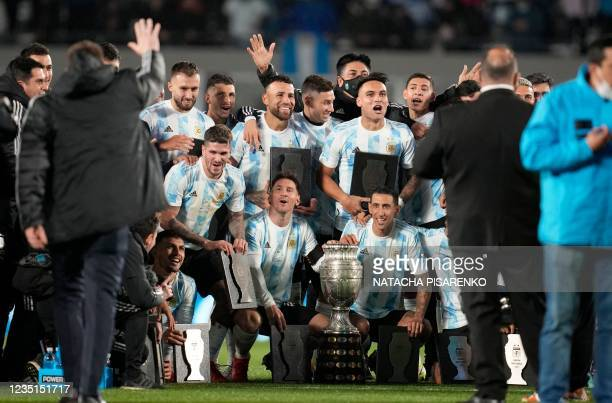 Argentina's players pose for a picture with the Copa America trophy at the end of their South American qualification football match for the FIFA...