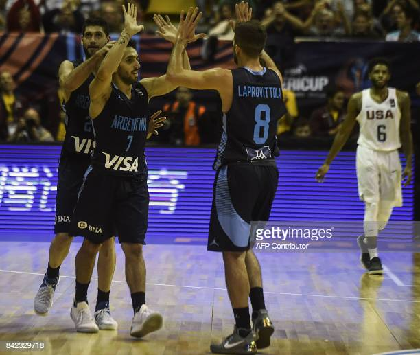 Argentina's point guard Facundo Campazzo celebrates with teammtes small forward Patricio Garino and point guard Nicolas Laprovittola after scoring...