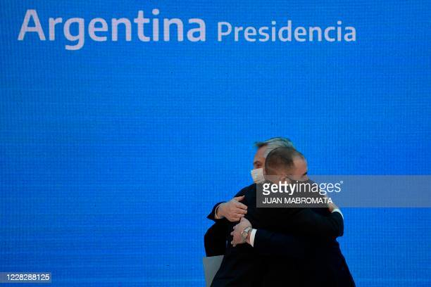 Argentina's President Alberto Fernandez and Economy Minister Martin Guzman embrace after announcing the restructure of a $66 billion foreign-law...