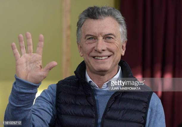 Argentina's President and presidential hopeful for the Juntos por el Cambio party Mauricio Macri waves before voting during the primary elections in...