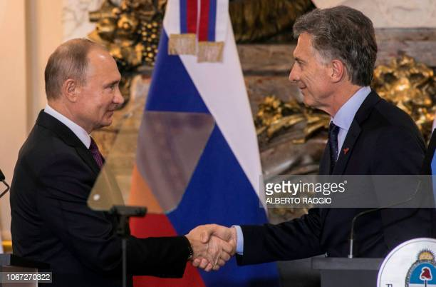 Argentina's President Mauricio Macri and Russia's President Vladimir Putin shake hands after a joint press conference at the Casa Rosada presidential...