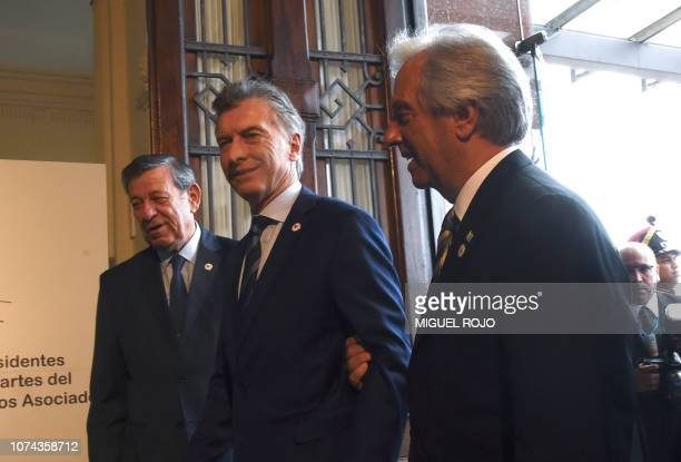 Argentina's President Mauricio Macri is welcomed by Uruguay's President Tabare Vazquez and Uruguay's Foreign Affairs Minister Rodolfo Nin Novoa...