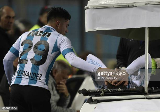 Argentina's Racing Club forward Brian Fernandez comforts injured teammate forward Lautaro Martinez during the Copa Sudamericana first stage second...