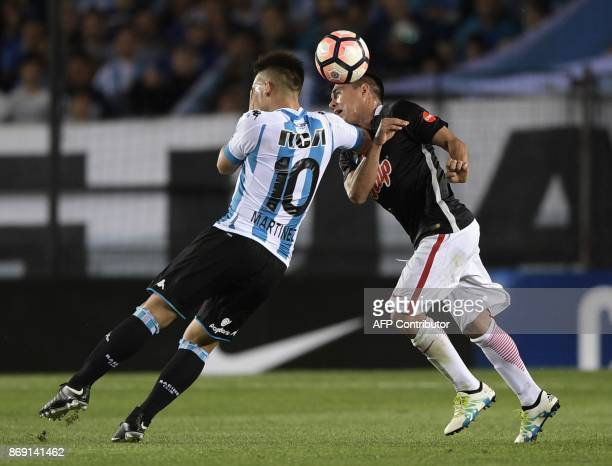 Argentina's Racing Club forward Lautaro Martinez vies for the ball with Paraguay's Libertad midfielder Angel Lucena during their Copa Sudamericana...