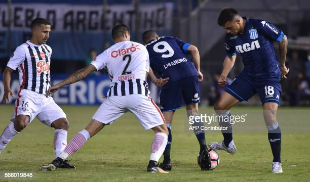 Argentina's Racing Lisandro Lopez and Enrique Triveiro vies for the ball with Paraguay's Libertad Alan Benitez and Segio Aquino during their...