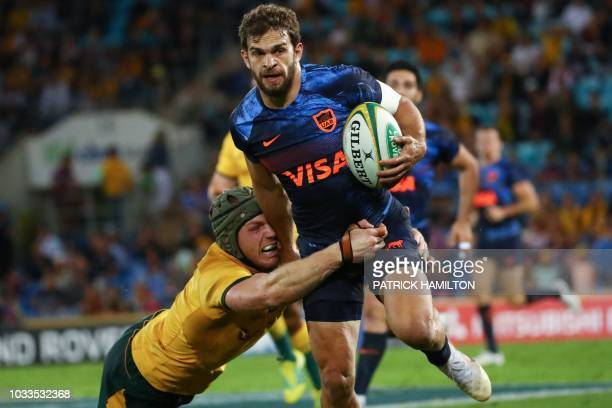 TOPSHOT Argentina's Ramiro Moyano beats the diving tackle of Australia's David Pocock during the Rugby Championship match between Australia and...