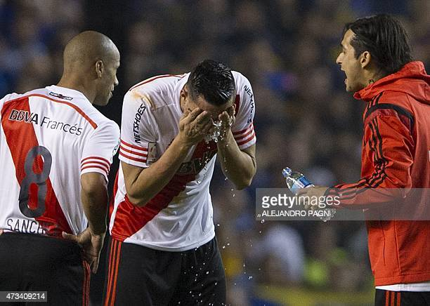 Argentina's River Plate defender Ramiro Funes Mori pours water on his face after getting reached by tear gas before the start of the second half of...