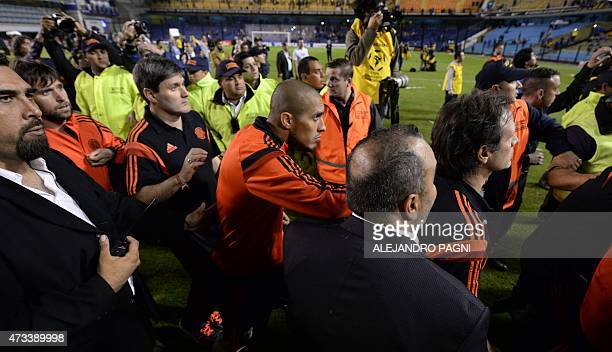 Argentina's River Plate footballers leave the pitch under police shields after the match was suspended when Boca Juniors' fans pepper sprayed River...