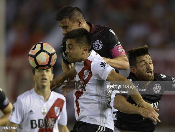 Argentina's River Plate forward Gonzalo Martinez vies for the ball with Argentina's Lanus defender Maximiliano Velazquez and forward Lautaro Acosta...