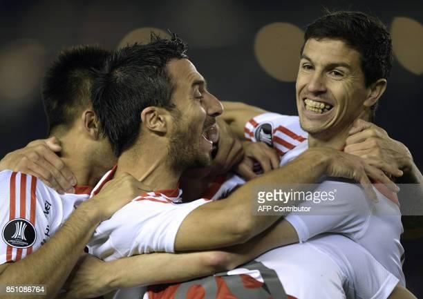 Argentina's River Plate forward Ignacio Scocco celebrates with teammates forward Gonzalo Martinez and midfielder Ignacio Fernandez after scoring his...