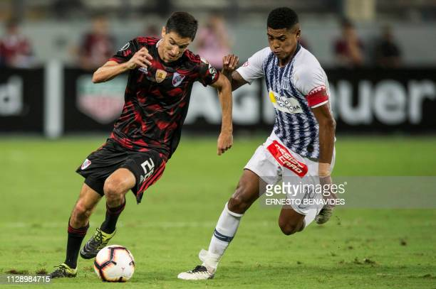 Argentina's River Plate Ignacio Fernandez vies for the ball with Wilder Cartagena from Peru's Alianza Lima during their Libertadores Cup football...