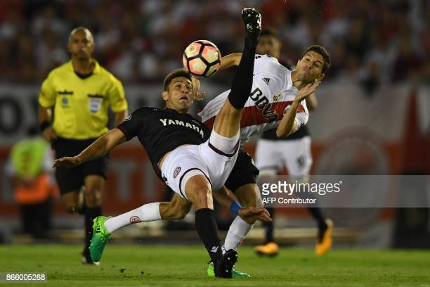 Argentina's River Plate midfielder Ignacio Fernandez vies for the ball with Argentina's Lanus defender Diego Braghieri during their Copa Libertadores...