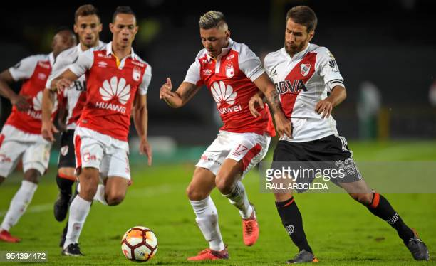 Argentina's River Plate player Leonardo Ponzio vies for the ball with Colombia's Independiente Santa Fe player Juan Roa during their Copa...