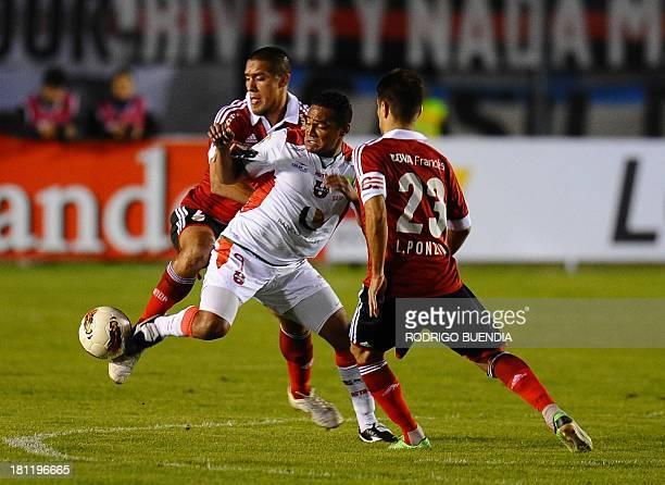 Argentina's River Plate players Leonardo Ponzio and Jonathan Maidana vie for the ball with Ecuador's Liga de Loja player Fabio Renato during their...