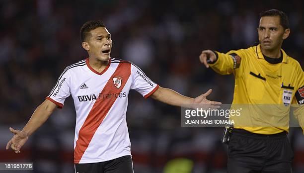 Argentina's River Plate's forward Teofilo Gutierrez complains next to Paraguayan referee Julio Quintana during the Copa Sudamericana 2013 round...