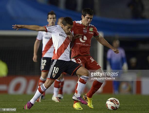 Argentina's River Plate's midfielder Manuel Lanzini vies for the ball with Ecuador's Liga de Loja's defender Oscar Ayala during their Copa...