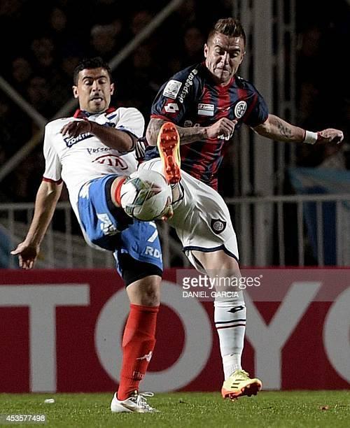 Argentina's San Lorenzo defender Julio Buffarini vies for the ball with Paraguay's Nacional forward Julian Benitez during their Copa Libertadores...