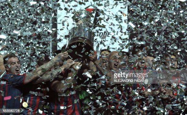 Argentina's San Lorenzo players hold up the trophy after winning the Copa Libertadores 2014 final second leg football match against to Paraguay's...