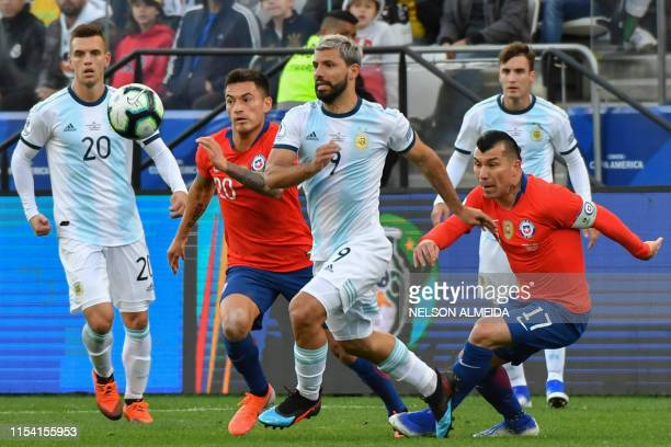 Argentina's Sergio Aguero and Chile's Charles Aranguiz and Gary Medel run for the ball during their Copa America football tournament thirdplace match...
