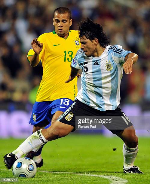 Argentina's Sergio Aguero vies for the ball with Daniel Alves of Brazil during their 2010 FIFA World Cup qualifier at the Gigante de Arroyito stadium...